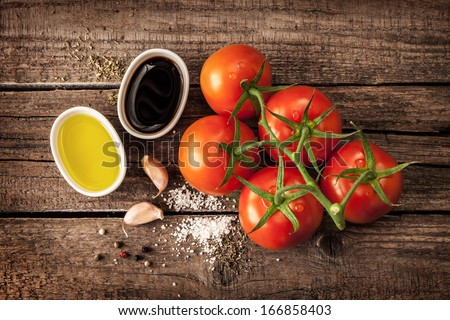 Vinaigrette or french dressing recipe ingredients and tomato branch on vintage wood background. Olive oil, balsamic vinegar, garlic, salt and pepper from above. - stock photo