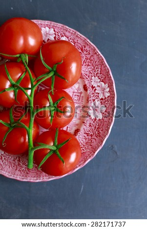 vine tomatoes are placed on a red printed plate on a grey background - Top down  - stock photo