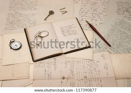 vintage accessories and open book over old letters and postcards. nostalgic background - stock photo