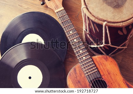 Vintage acoustic guitar, drum and vinyl record on a wooden background - stock photo