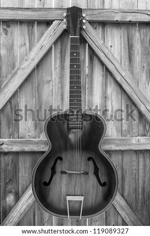 Vintage acoustic guitar hanging on an old, crooked, weather-beaten fence, monochrome. - stock photo
