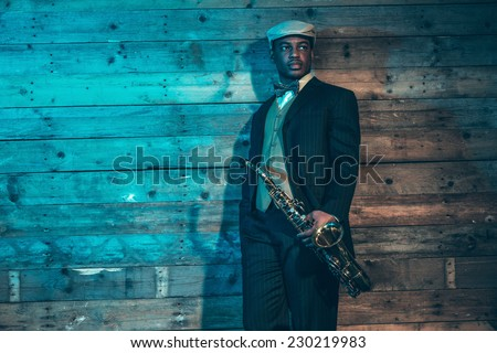 Vintage african american jazz musician with saxophone in front of old wooden wall. Wearing suit and cap. - stock photo