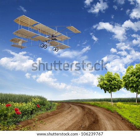 vintage airplane in flight over a field - stock photo