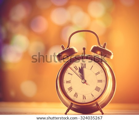 Vintage alalm clock on yellow background with bokeh - stock photo