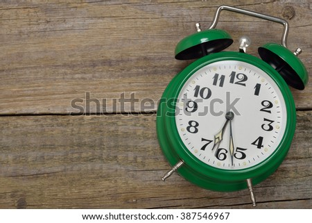 Vintage alarm clock on a wooden background - stock photo
