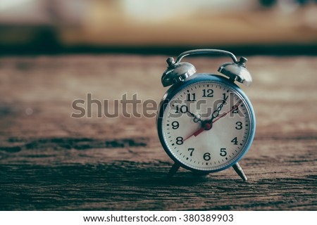 Vintage alarm clock on weathered wood background - stock photo