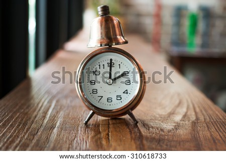 vintage alarm clock on wooden table and Instagram filter  shallow depth of field / Background defocus - stock photo