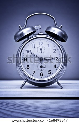 Vintage alarm clock on wooden table at night, insomnia concept. - stock photo