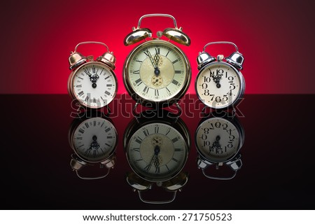 Vintage alarm clocks showing five minutes to twelve, red background - stock photo