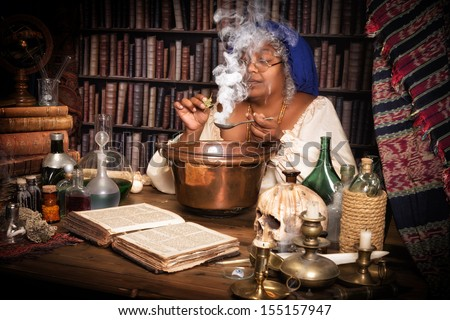 Vintage alchemist adding herbs to a smoking kettle - stock photo