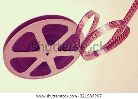 Vintage analog photographic film strip wheel isolated on white background. - stock photo