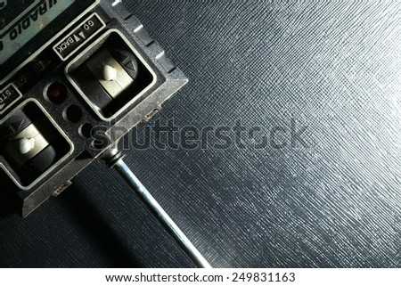 Vintage and dirty radio controller unit put on the black color leather background represent the radio controller equipment and accessory related. - stock photo