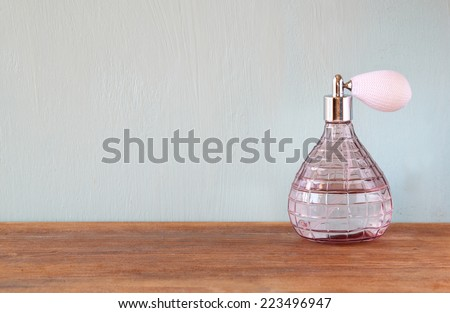 vintage antique perfume bottle with old picture frame, on wooden table. - stock photo