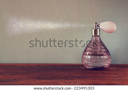 vintage antique perfume bottles, on wooden table. retro filtered image - stock photo