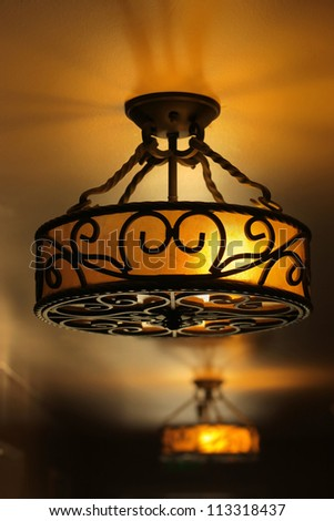 Vintage art deco ceiling lamp fixture in dark hallway - stock photo