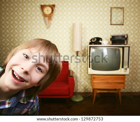 vintage art portrait of liitle boy looking out at camera in room with interior from 70s, retro stylization, toned - stock photo