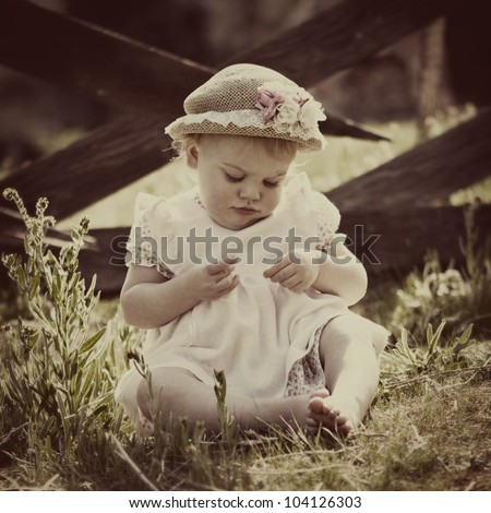 Vintage Baby: beautiful little girl in old-fashioned hat and dress - stock photo