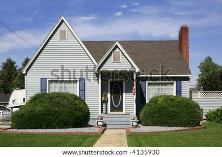 Vintage baby blue house with shutters and red brick trim - stock photo