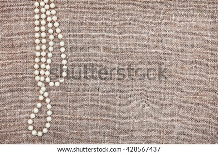 Vintage background with bead necklace on the old rude burlap - stock photo