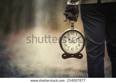 Vintage Background with man holding retro alarm clock in hand. - stock photo