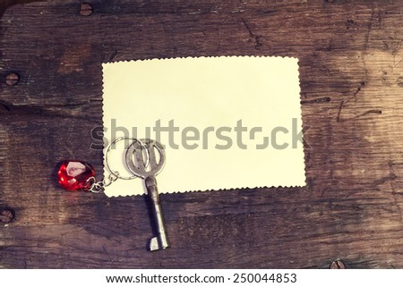Vintage background with old key and a note - stock photo
