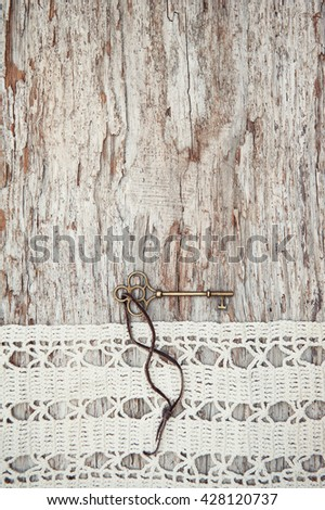 Vintage background with old key and lace on the rude weathered wood - stock photo