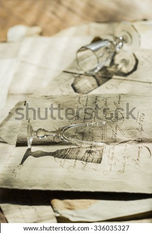 Vintage background with old paper, calligraphy handwriting letters and two liqueur glass - stock photo