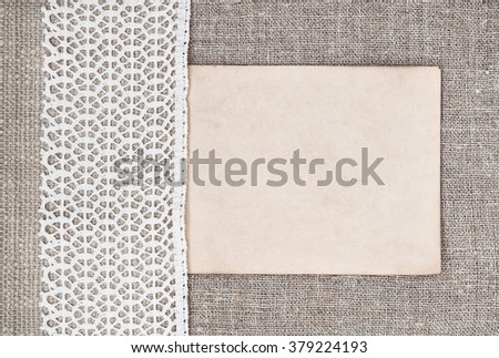 Vintage background with old paper on lace fabric and burlap cloth - stock photo