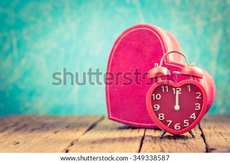 Vintage background with red heart alarm clock on table - stock photo