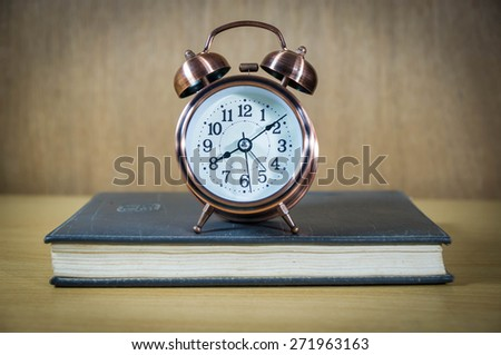 Vintage background with retro alarm clock and book on table - stock photo