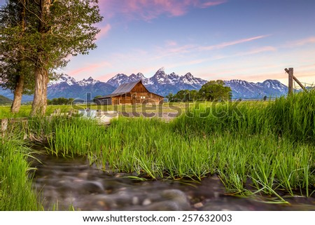Vintage barn sits in front of the Grand Teton Mountains, Wyoming. - stock photo