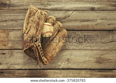 Vintage baseball mitt and ball on grungy, rough wood background viewed from above - stock photo