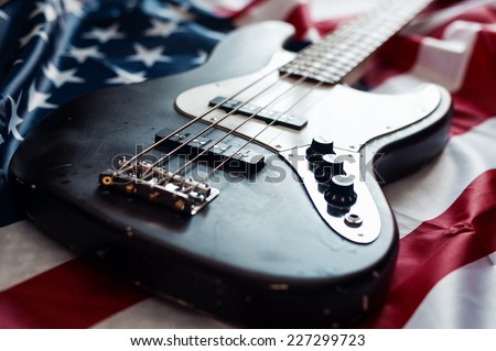 Vintage bass guitar on an american flag background with selective focus - stock photo