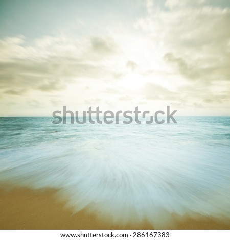 Vintage beach scene in sunset, slow shutter with moving waves. - stock photo