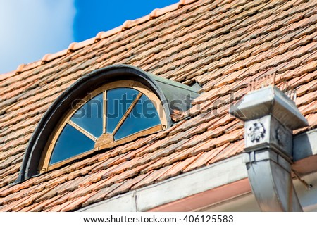 Vintage beautiful window in the attic under the roof of the house - stock photo