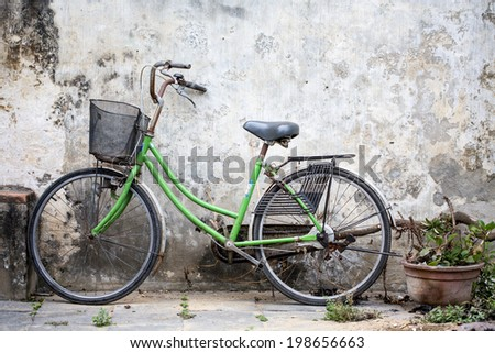 Vintage Bicycle Against Grunge Wall - stock photo
