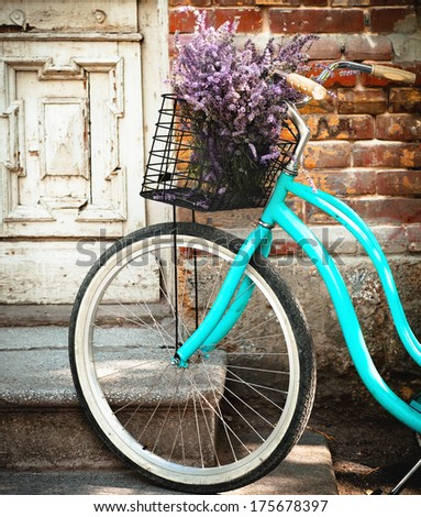 Vintage bicycle with basket with lavender flowers near the old wooden door - stock photo