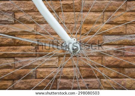 Vintage bike, Bicycle Wheel over brick wall background - stock photo