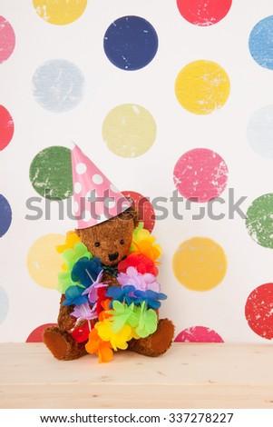 vintage birthday bear in colorful nursery room - stock photo