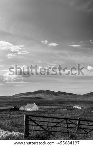 Vintage black and white landscape of Staffin, Isle of Skye, Scotland with rural houses, a sky with clouds and a fence in the foreground and hills in the distant background - stock photo