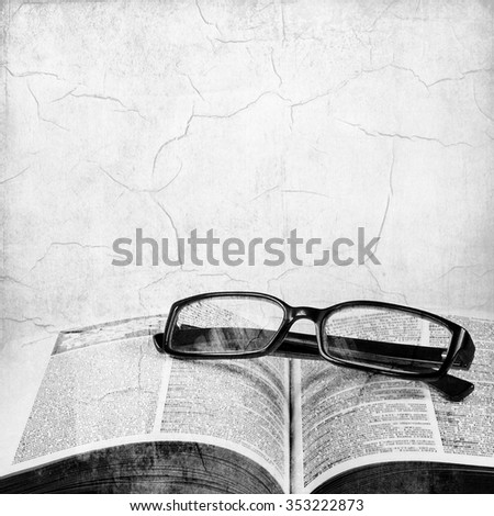 Vintage black and white open book and classic eyeglasses - stock photo