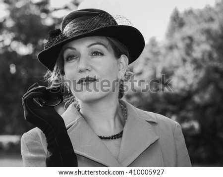 Vintage black and white portrait of a woman with a suit and a black hat looking dreamily - stock photo