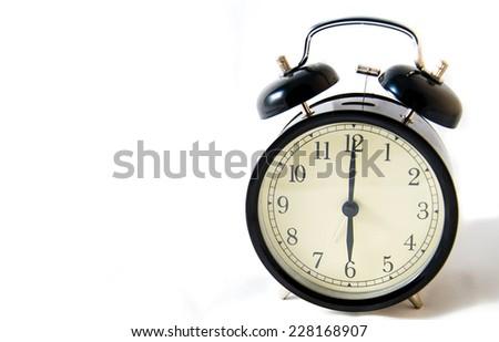 Vintage black clock on a white illuminated background at six o'clock - stock photo