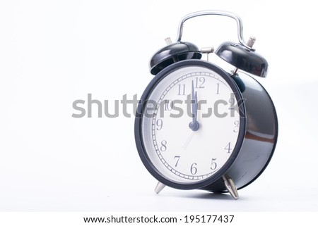 Vintage black color alarm clock on the write background - stock photo