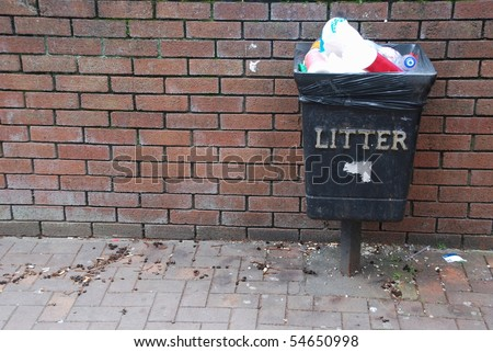 vintage black garbage can on a brick wall background - stock photo