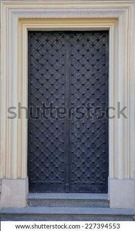 Vintage black iron door to church  - stock photo