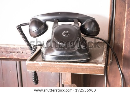 Vintage black phone on old wooden table background - stock photo