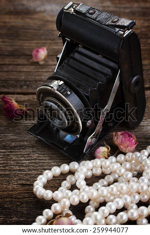 vintage black photo camera  with pearl strands on wooden background - stock photo