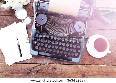 Vintage black typewriter on decorated wooden table, outdoors, close up - stock photo
