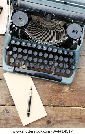 Vintage black typewriter with papers and pen on wooden table, outdoors - stock photo